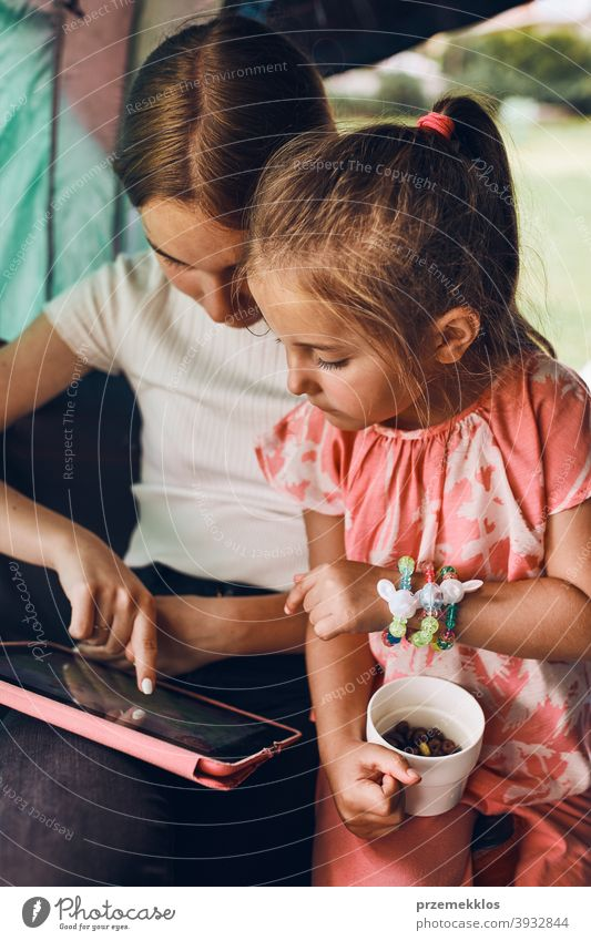 Sisters spending time in a tent on camping. Children using tablet playing games online during summer vacation children girl siblings sister family internet