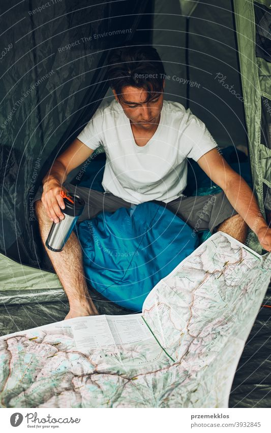 Young man looking at a map of mountain trails planning next trip on summer vacation sitting in a tent on camping examining tourist travel copy space wanderlust