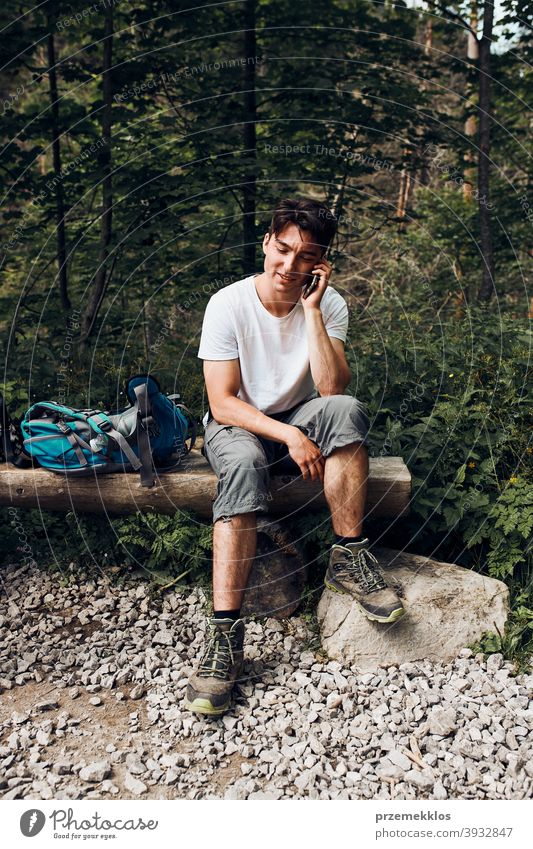 Young man with backpack talking on phone having break sitting on trunk during hike in a mountains activity adventure forest forest landscape forest path freedom
