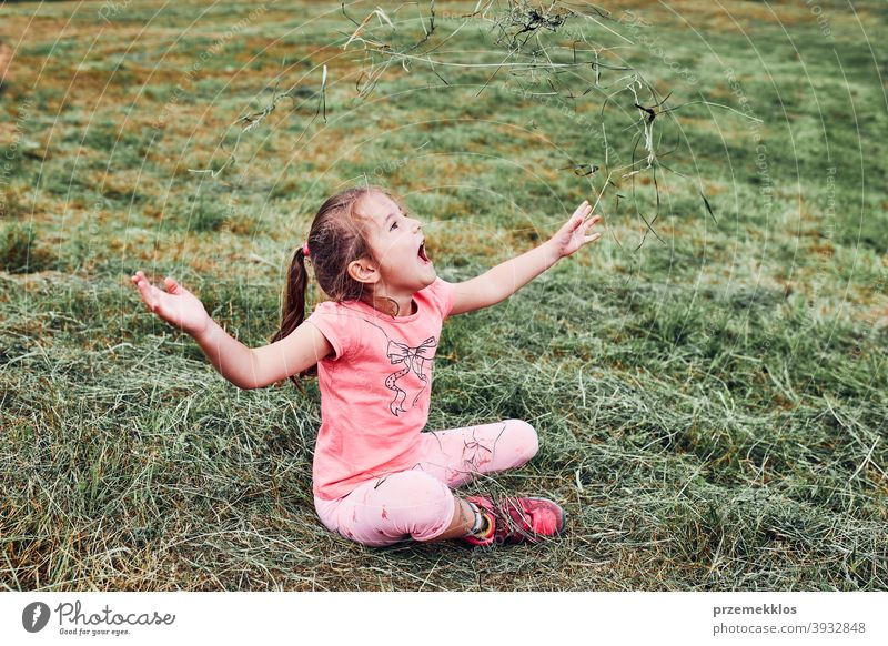 Little girl playing with grass enjoying summer day playing in the field during vacation trip happy excitement enjoyment leisure emotion positive lying lifestyle