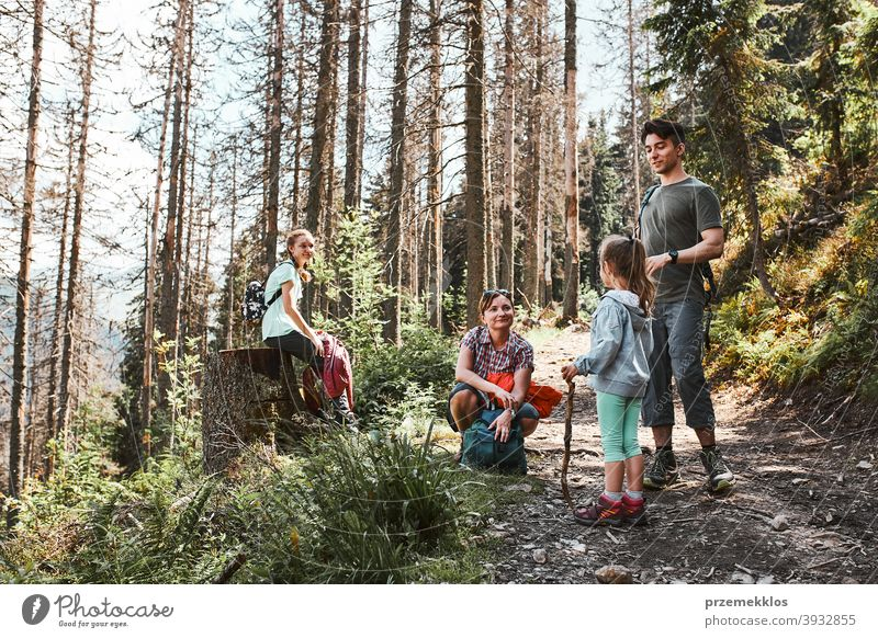 Family with backpacks hiking in a mountains actively spending summer vacation together activity adventure female forest forest landscape forest path freedom fun