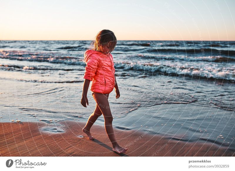 Little girl walking barefoot on a beach at sunset free enjoy positive emotion carefree nature outdoors travel happiness happy sea summer vacation leisure fun