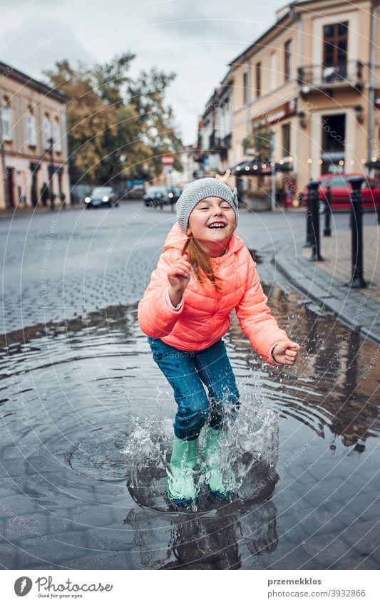 Little girl holding big umbrella jumping in the puddle on rainy gloomy autumn day raining outdoors little seasonal fall childhood beautiful weather outside kid