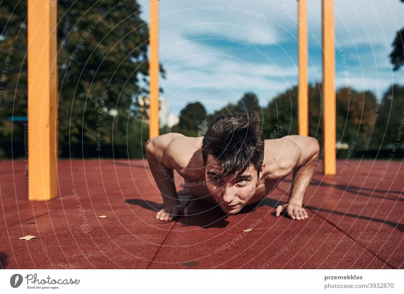 Young shirtless man bodybuilder doing push-ups on a red rubber ground during his workout in a modern calisthenics park care caucasian health lifestyle male one
