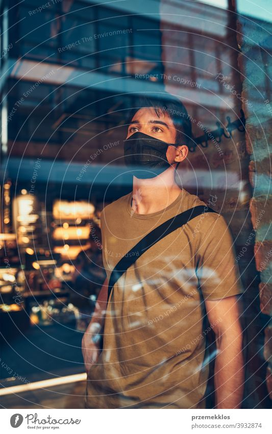 Young man standing in coffee shop at store front in the city center, wearing the face mask to avoid virus infection caucasian conversation covid-19 lifestyle
