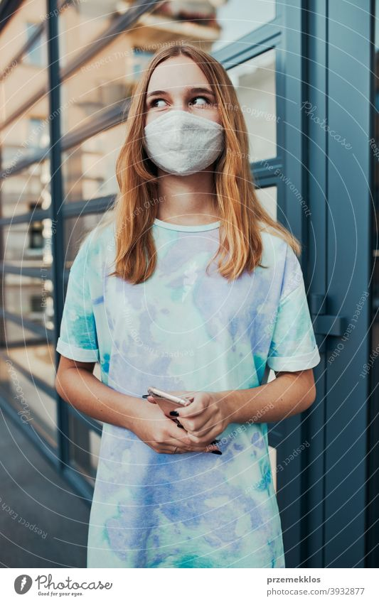 Portrait of young woman girl standing at store front downtown wearing face mask to avoid virus infection caucasian cellphone conversation covid-19 female