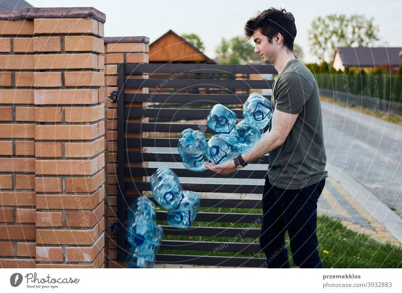 Young man throwing out empty used plastic water bottles into trash bin blue collect collecting container crushed disposal ecology environment female garbage