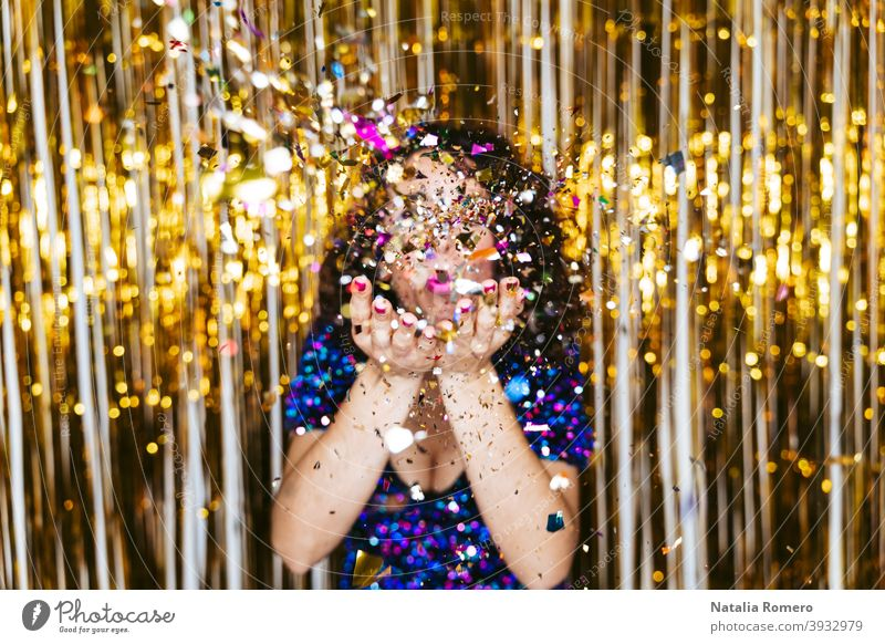 Selective focus. A woman in an elegant shiny dress and Christmas decorations behind her blowing some confetti to the camera. New Year's Eve party concept