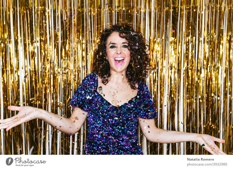 A beautiful woman in elegant clothes with Christmas decorations behind her celebrating New Year's Eve while some confetti is falling above her. New Year's Eve party at home concept