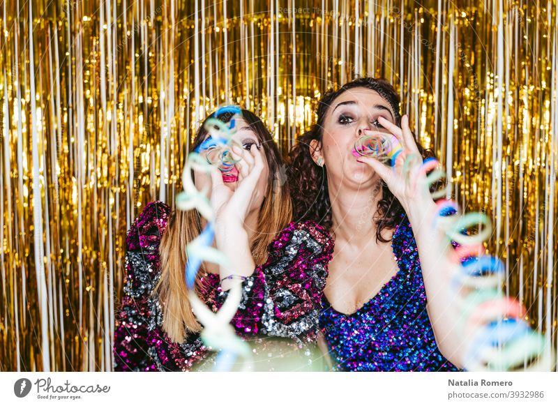 Two beautiful women in elegant clothes with Christmas decorations behind them blowing streamers to the camera while celebrating in a New Year's party. New Year's Eve party concept