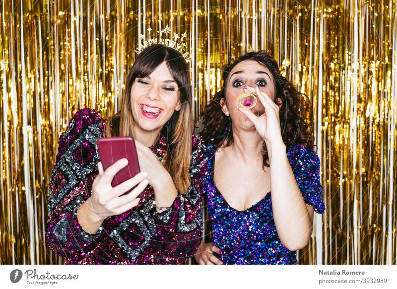 Two beautiful women with party clothes and Christmas headbands having fun together in a New Year's Eve party with some portraits of them. New Year's Eve concept