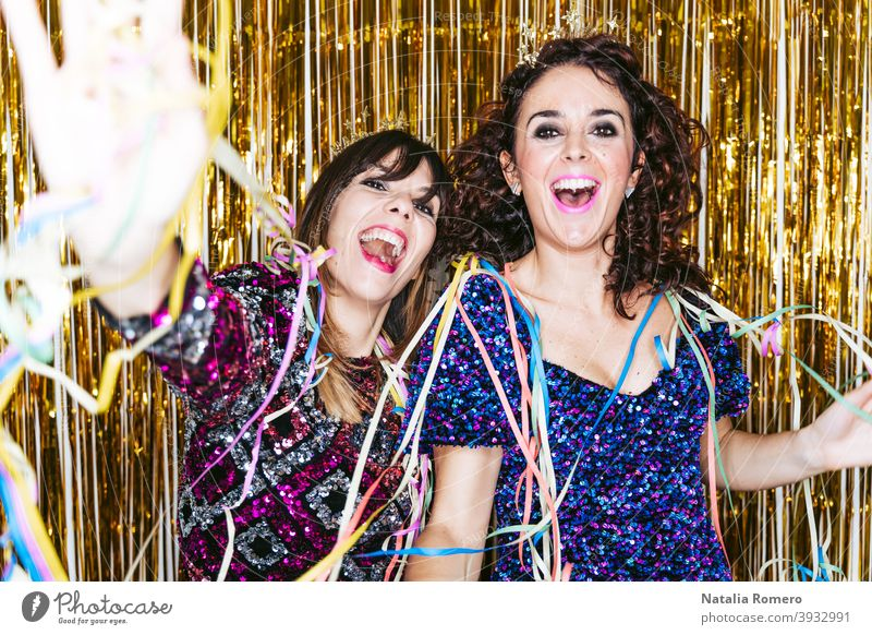 Two beautiful brunette women in elegant clothes and decorations behind them celebrating the end of the year together while playing with some streamers. New Year's Eve party at home concept