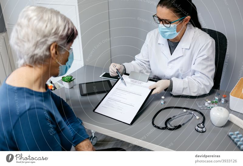 Doctor explaining to her patient consent form to coronavirus vaccine doctor doctors office pointing side effects benefits risks vial covid-19 showing