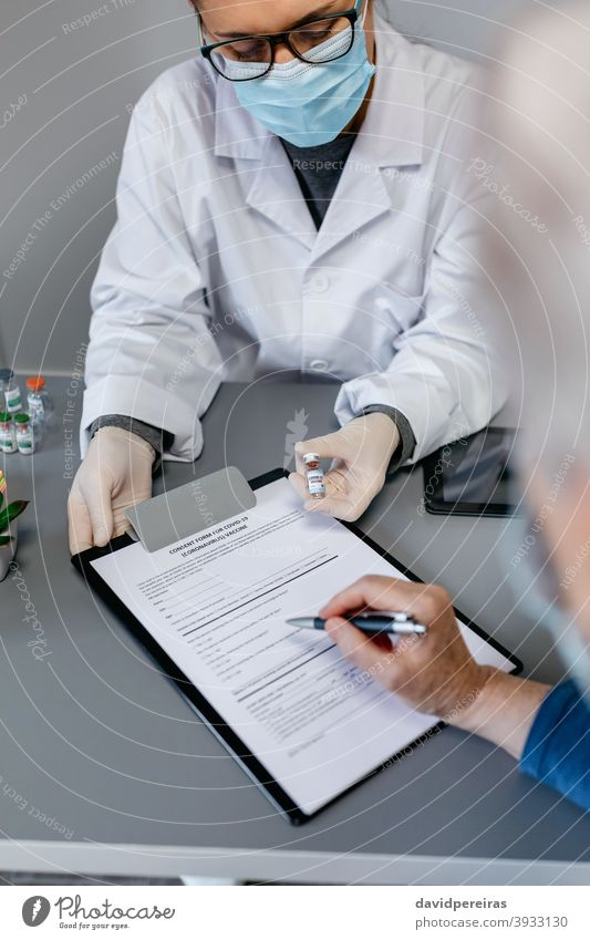 Doctor explaining to her patient the benefits and risks of the coronavirus vaccine doctor possible adverse effects vial consent form covid-19 showing fill