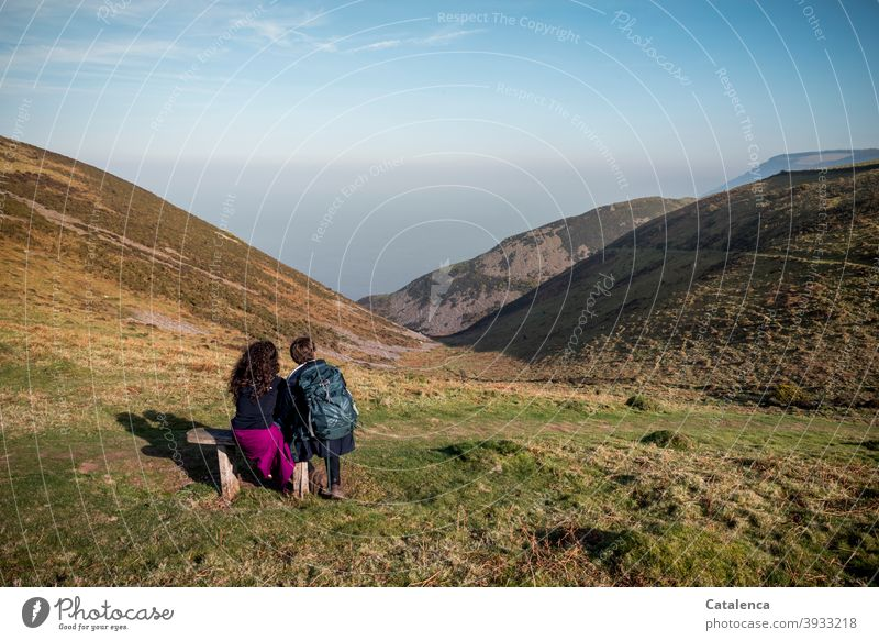 Young couple sitting on a bench enjoying the sea view during a hiking break Nature Landscape Ocean Hill cliffs Plant Grass bushes Wooden bench Sit Observe