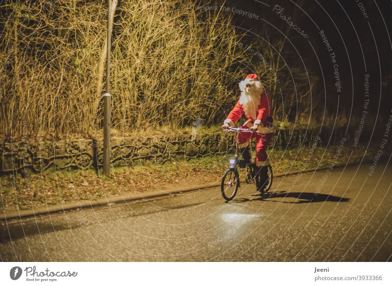 There he came cycling on Christmas Eve | Santa Claus on the bike | because there was no snow, he could not use the sleigh | with mouth-nose-protection because of the Corona-pandemic