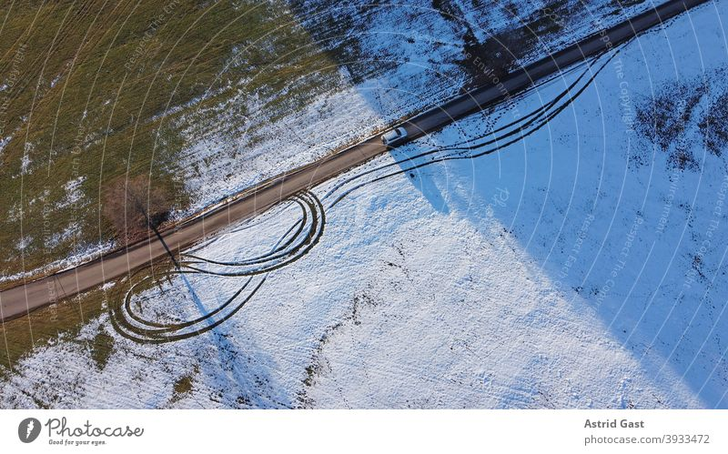 Drone photo of a white car driving from light to shadow on a road in winter Aerial photograph drone photo Winter Street Driving Snow Sun Shadow Light Dark