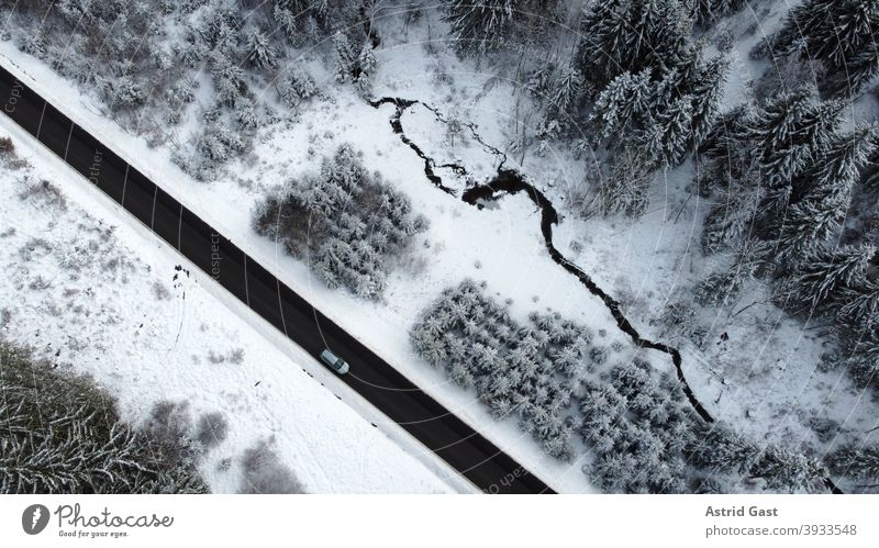 Aerial view with a drone of a road with a car driving through the forest in the winter time Aerial photograph drone photo Winter Street Driving Snow Forest