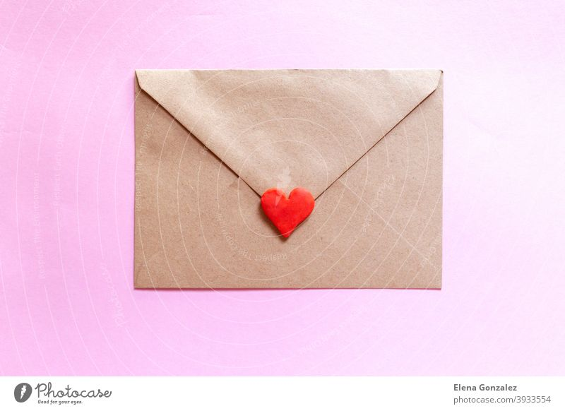 Love letter in a craft envelope with clay red heart on pink background. craft paper symbols mail elements ideas relationship details lover send address