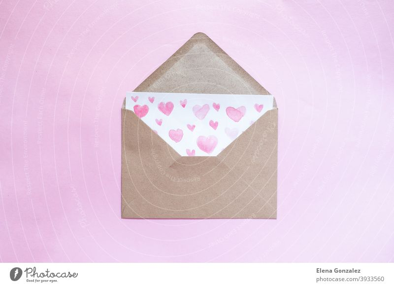 Love letter with water color pink hearts in a craft envelope on pink background. craft paper symbols mail elements watercolor ideas relationship details lover