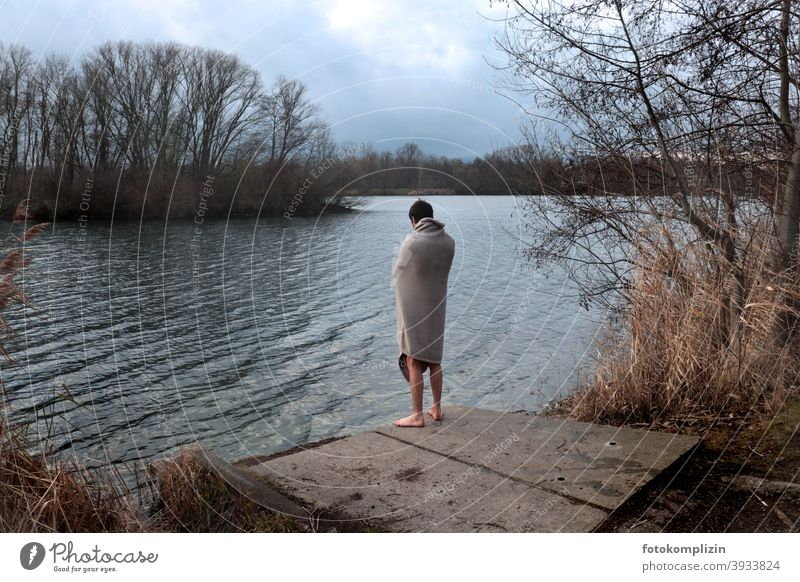 Young man wrapped naked in blanket in winter, looking at a lake Ice Swimming Winter Bathing Ice bathing salubriously Winter's day bathe chill Rear view