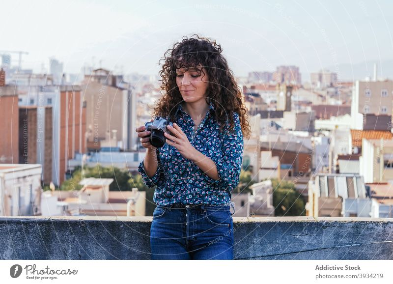 Smiling photographer on rooftop in city woman photo camera look through building cityscape female style gadget modern content urban smile memory moment lady