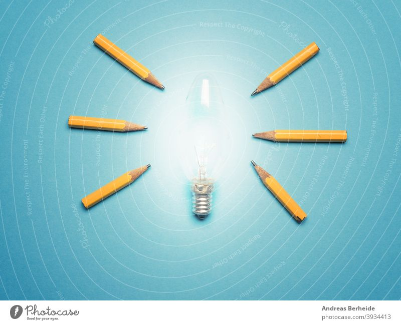 A glowing light bulb with 6 pencils as light rays, New ideas or creativity concept on blue background diversity team positive opportunity individuality finance