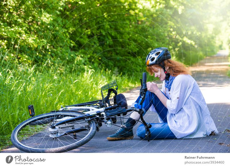 a woman had an accident, she fell with a bicycle and hurt herself Accident Bicycle bicycle accident Sudden fall violation cyclist Helmet Knee Street off Summer