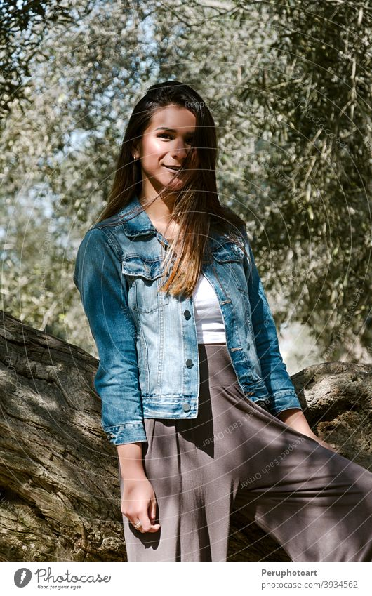 Beautiful long-haired teen woman with brown hair leaning on a tree female green nature brunette grass trunk casual countryside denim grassland long hair