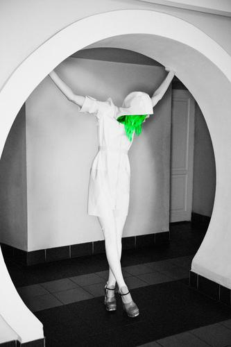 Green hair - don't care. Even though the whole image is black & white. Latex fashion photoshoot featuring a female model with enormously long legs in high heels and a white raincoat with a hoodie.