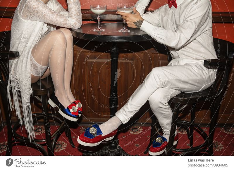 It's a date and these two young people are flirting all over the table. Dressed in white with avant-garde shoes all shining from far away they're having glasses of milk. The red carpet represents this fancy restaurant as a perfect place for flirting.