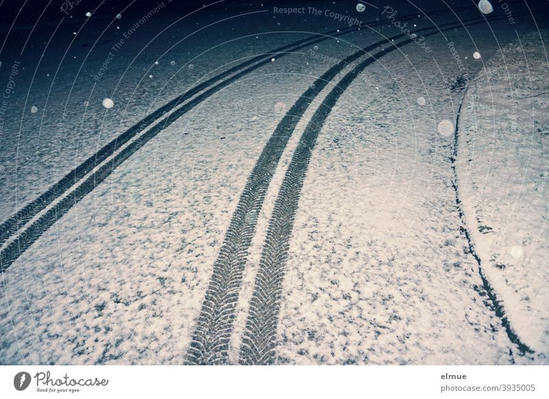 tire tracks of a car running in an arc on a lightly snow-covered road in the nocturnal flake swirl / winter / slippery roads Car track Winter Snow