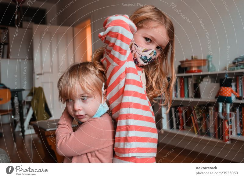 Sibling Sisters Posing Back to Back cloth mask child sisters kid children female girl Indoor home at home siblings back to back caucasian face mask protective