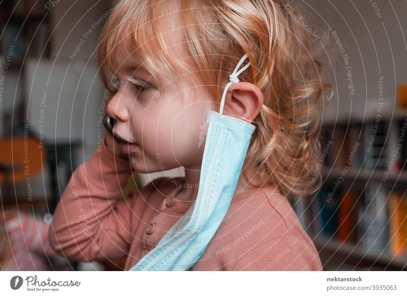 Child with Face Mask Hanging from Ear mask child kid female girl Indoor home at home caucasian face mask protective 2020 lockdown quarantine real life