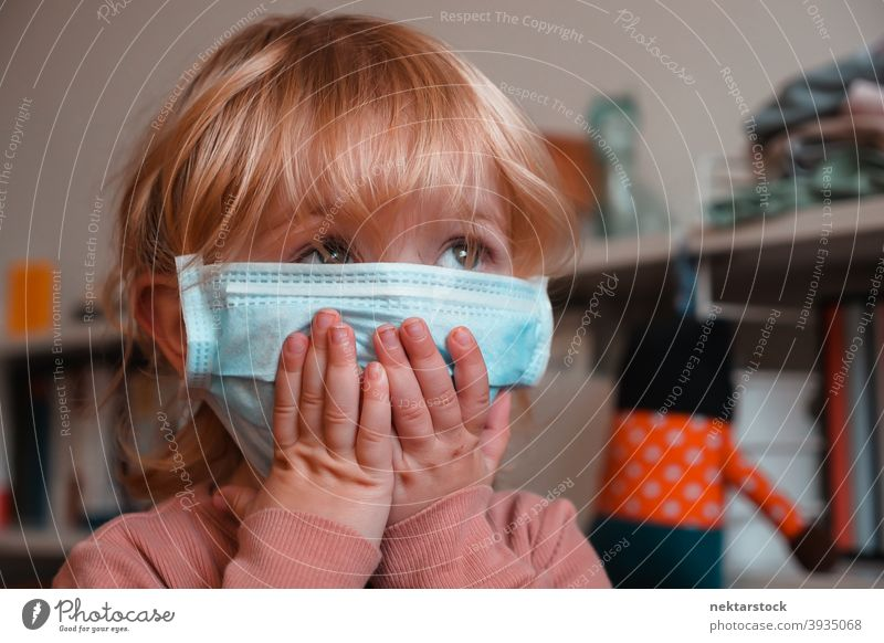 Child Covering Face with Mask surgical mask child kid face obscured female girl Indoor home at home caucasian face mask protective 2020 lockdown quarantine