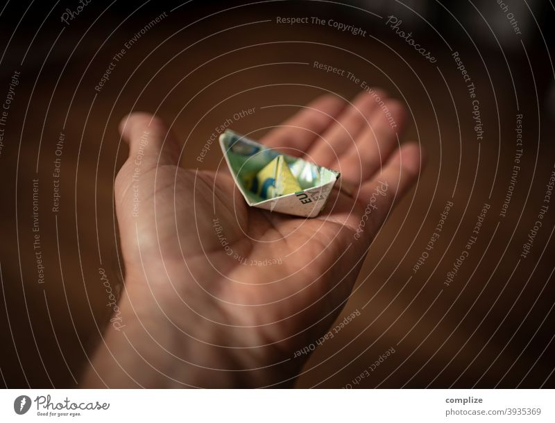 A paper ship made of a euro banknote on one hand Playing Handicraft Relaxation Healthy insulation Freedom Tourism Cruise Model-making Future Infancy Paper boat