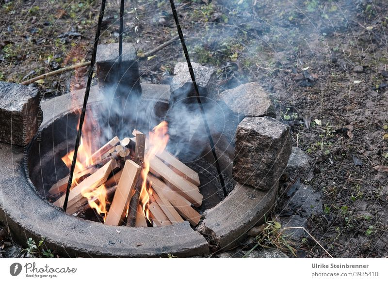Lighting a campfire for cooking Fire Firewood Logs cooking fire Tripod start a fire Burn blaze fire up Ignite Hot Wood Fireplace Warmth Smoke