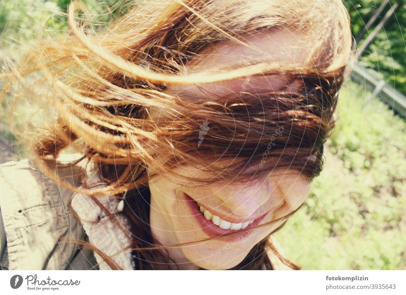 Portrait of a smiling woman with flying hair in front of her eyes Face windy Identity Looking Woman portrait Long-haired naturally hairstyle take a walk out