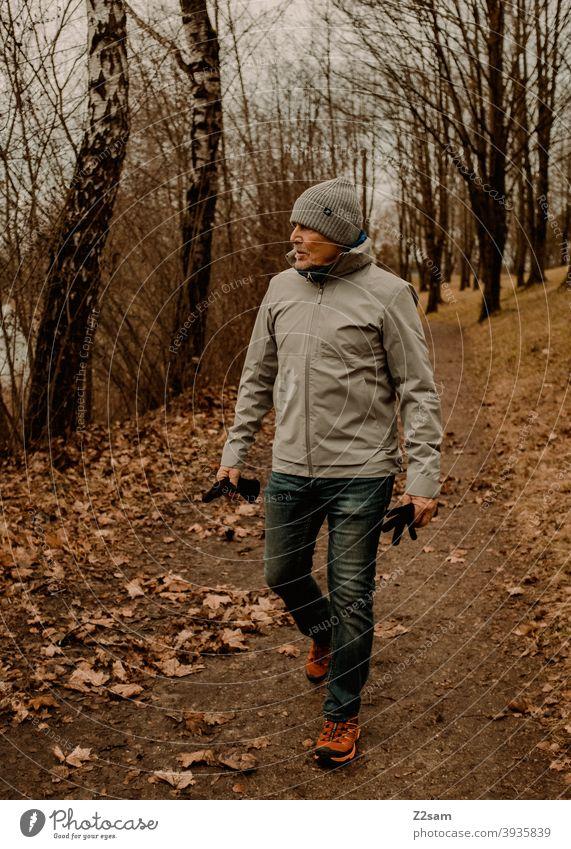Sportlicher Rentner in der Natur beim spaziergen gehen spazieren natur outtdoor sport sportlich rentner alter mann portrait mütze winter kälte landschaft wald