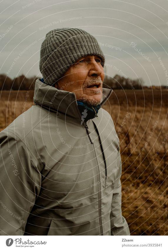Portrait eines sportlichen Rentners in der Natur spazieren natur outtdoor rentner alter mann portrait mütze winter kälte landschaft wald sträucher freizeit