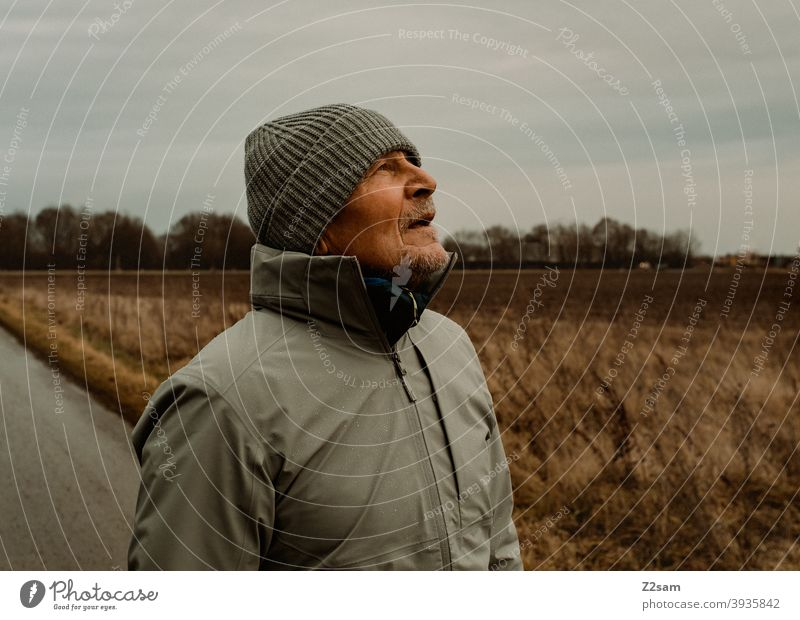 Sportlichen Rentner mit Blick nach oben in der Natur spazieren natur outtdoor sport sportlich rentner alter mann portrait mütze winter kälte landschaft wald