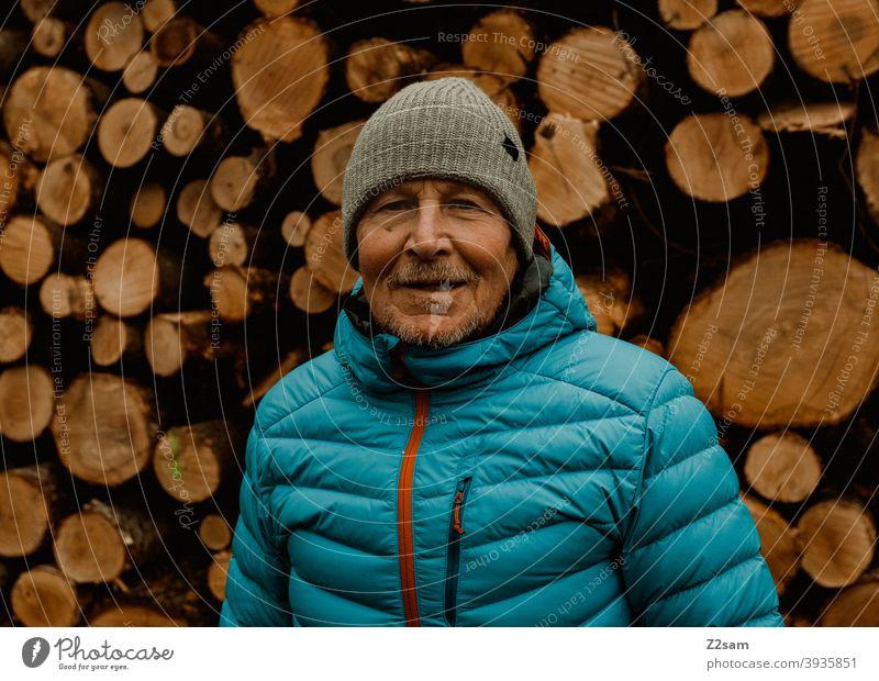 Portrait eines sportlichen Rentners vor einem Holzstapel spazieren natur outtdoor rentner alter mann portrait mütze winter kälte landschaft wald sträucher isar