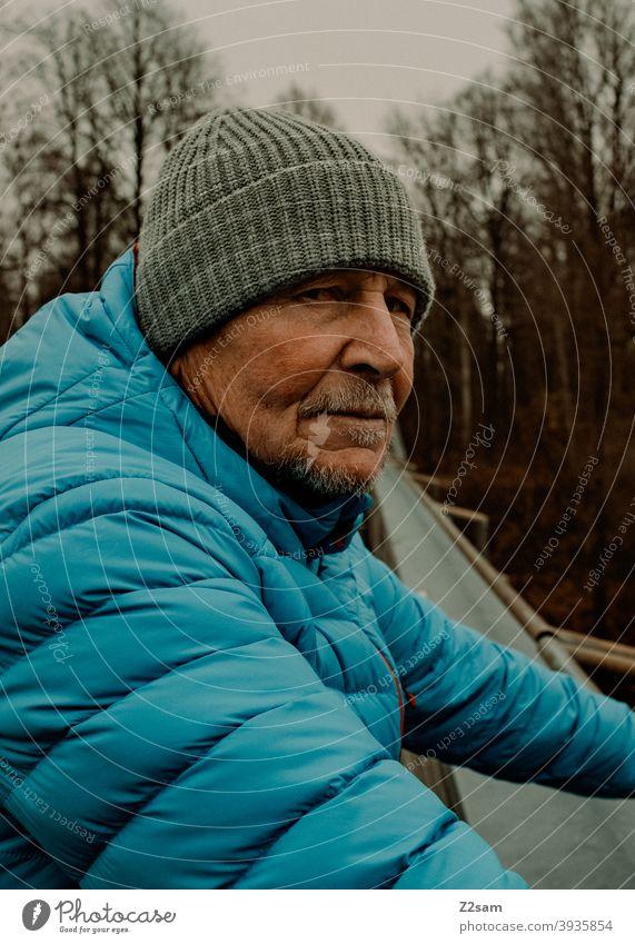 Skeptischer Blick eines sportlichen Rentners in der Natur spazieren natur outtdoor rentner alter mann portrait mütze winter kälte landschaft wald sträucher isar