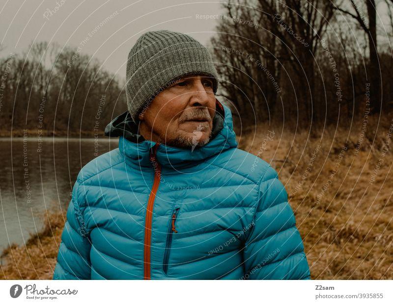 Portrait eines sportlichen Rentners in der Natur spazieren natur outtdoor rentner alter mann portrait mütze winter kälte landschaft wald sträucher isar freizeit