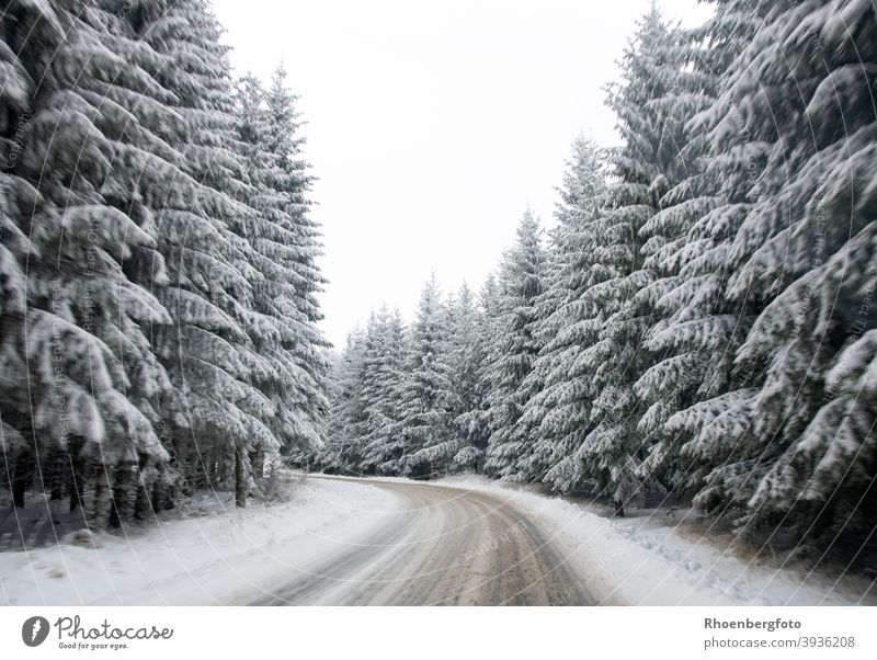 slippery snow covered road in a forest area Street Snow Forest firs conifers Winter Landscape Nature Winter maintenance program broaching Push Salt smooth peril