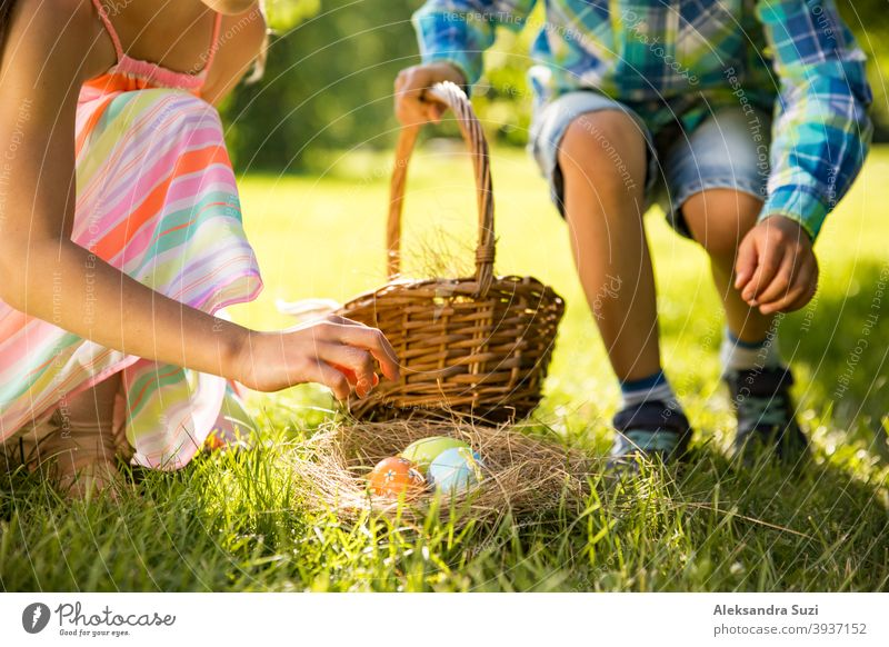 Cute boy and girl celebrating Easter, searching and eating chocolate eggs. Happy family holiday. Happy kids laughing, smiling and having fun. Beautiful spring sunny day in park
