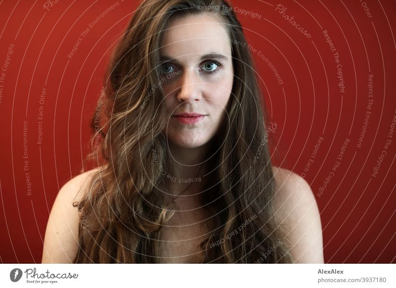 Portrait of a young woman with big green eyes in front of a red wall Young woman Central perspective Expectation Day Intensive Wall (building) Red salubriously
