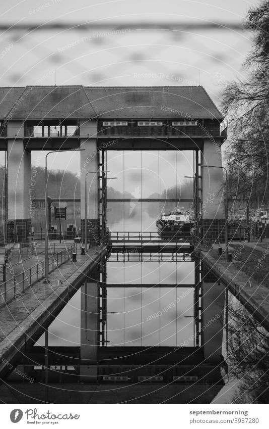 Lock gate with water and ship in the background Autumn Haze Lock system black-white Deserted Exterior shot Barge