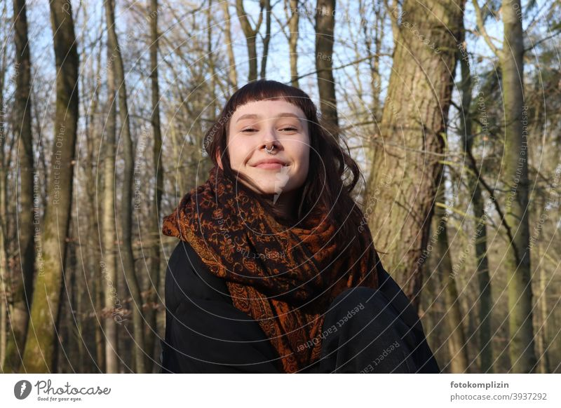 Portrait of young smiling woman with nose piercing under bare trees Young woman Face of a woman smilingly Impish feminine young adults youthful Brunette