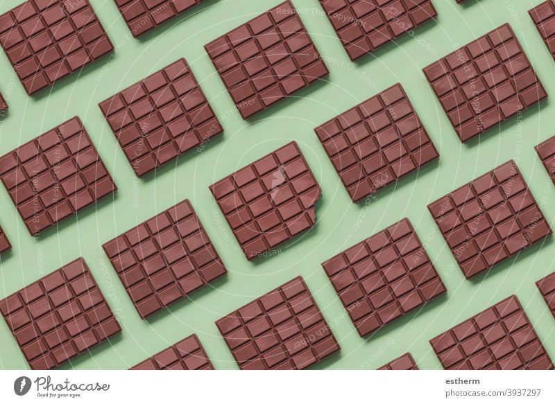 Geometric pattern made with chocolate bars and in the center a bitten tablet geometric pattern milk chocolate yummy confectionery broken antioxidan cacao powder